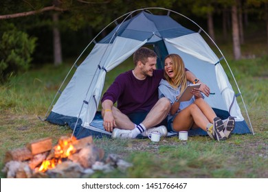 Young couple drinking coffee, enjoying the mountain view and checking the tablet with campfire in the sunset