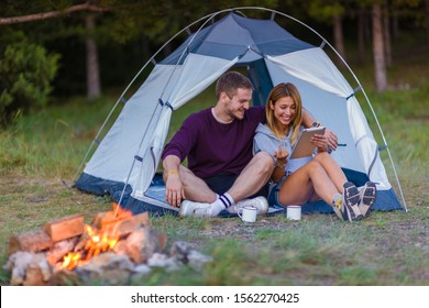Young couple drinking coffee, enjoying the mountain view and checking the tablet with bonfire in the sunset