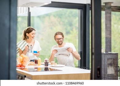Young couple drinking coffee and reading newspaper during a breakfast time sitting at the kitchen of the modern country house