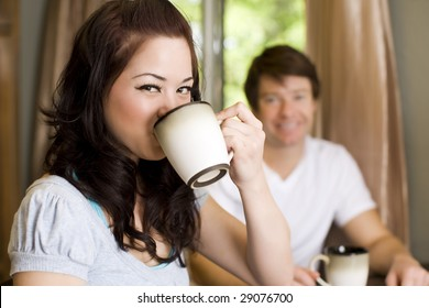 Young couple drinking coffee in their kitchen
