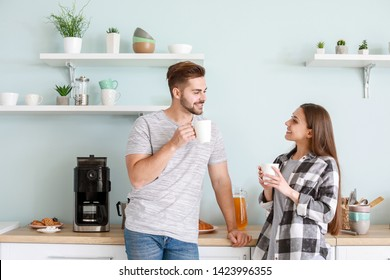 Young couple drinking hot coffee in kitchen