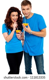 Young couple drinking orange juice together, sipping with straw