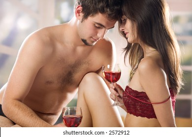 Young couple drinking red wine on the bed in bedroom