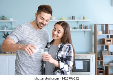 Young couple drinking tasty milk in kitchen at home