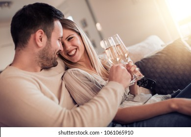 Young couple drinking wine together at home.