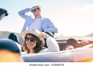 A young couple drives in a convertible and admires the landscape on vacation