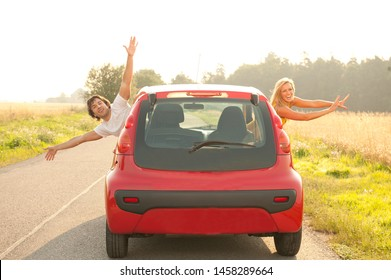 Young couple driving red car on a hot summer day