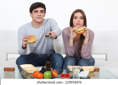 Young couple eating burgers