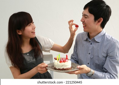 A young couple eating cake