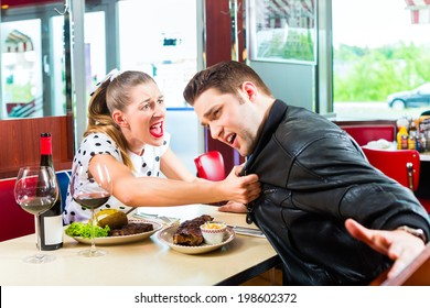 Young couple eating fast food and drinking red wine in a American retro fast food diner argues