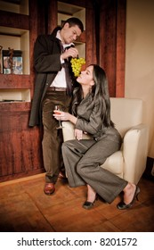 young couple eating grape, indoor