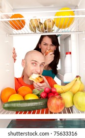 Young couple eating and looking at healthy fruit and vegetable in modern refrigerator, isolated on white background.