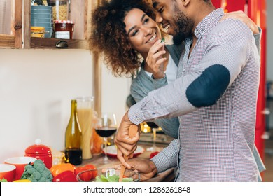 Young couple eating playfully vegetables kitchen, caring african-american woman feeding her cooking boyfriend, copy space
