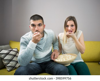 Young couple eating popcorn and watching a movie. They are sitting on the sofa.