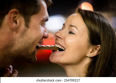 Young couple eating together one piece of chocolate - in street at night