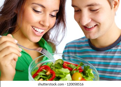 Young couple eating vegetable salad