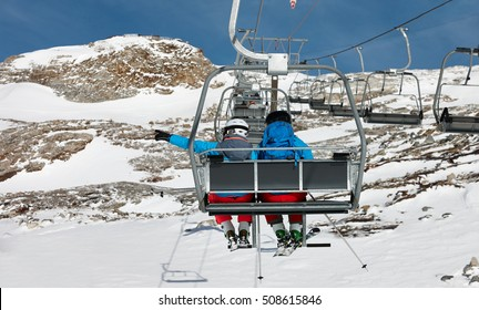 Young couple elevating on chairlift