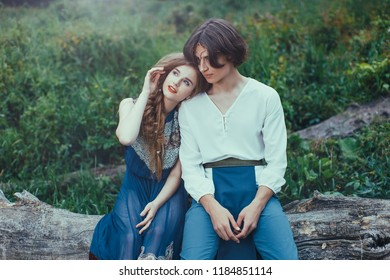 Young couple of elves in love siting on tree in magical forest outdoor on nature. Fairy tale love, relationship and magik people concept. Man and woman talking and looking away