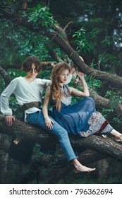 Young couple of elves in love siting on branch in magical forest outdoor on nature. Fairy tale love, relationship and magic people concept.