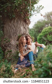Young couple of elves in love sitting in magical forest agaist the big tree outdoor on nature. Fairy tale of love, relationship and magik people concept. Man ambracing woman