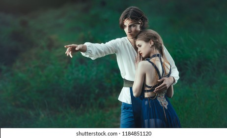 Young couple of elves in love standing in magical forest outdoor on nature. Fairy tale love, relationship and magik people concept. Man holding woman by hands and pointing away. Heroic look