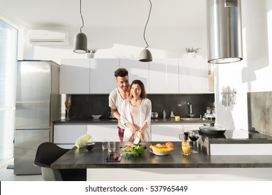 Young Couple Embrace In Kitchen, Hispanic Man And Asian Woman Hug Modern Apartment Interior