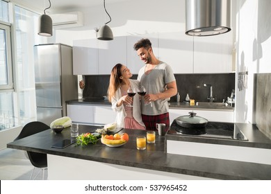 Young Couple Embrace In Kitchen, Hispanic Man And Asian Woman Hug Drink Wine Modern Apartment Interior