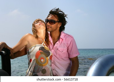 Young couple embraced in front of the sea
