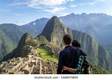 Young couple embracing contemplating the incredible landscape of Machu Picchu. The ruins of the citadel of Machu Picchu and Mount Huayna Picchu are seen