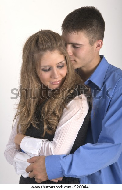 Young couple embracing with the guy's arms around her.