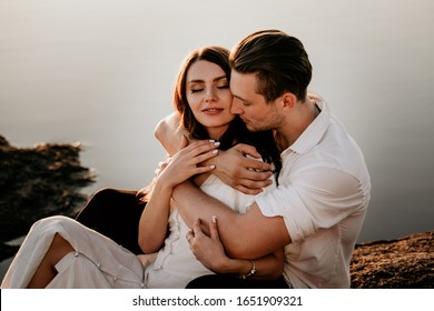 Young couple embracing and kissing on Sunset coast. Romantic love story. Brunette girl in a light dress.