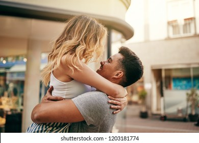 Young couple embracing and looking into each other's eyes while sharing a romantic moment on a city street