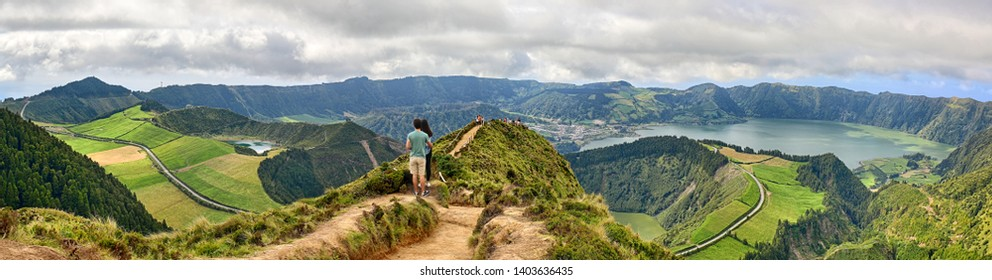 Young couple enjoy the panoramic view of Crater Sete Cidades from Pico da Cruz at Sao Miguel, Azores