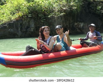 Young couple enjoy white water kayaking on the river, extreme and fun sport. People who are not wearing life jackets enjoy summer vacation activity. - Phuket Thailand June 2020 RFV