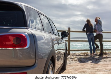 Young Couple Enjoying Beach View Besides Their Car