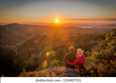 A young couple enjoying the beautiful sunrise on Mount Kaputar in New South Wales Australia