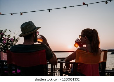 Young couple enjoying beer and sunset in a beach bar