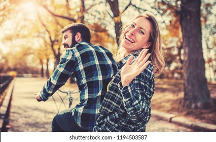 Young couple enjoying in a bike ride through the park. Love and tenderness, dating, romance. Lifestyle concept