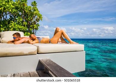 Young couple enjoying the blue sea on Santorini island, Greece from their hotel terrace.