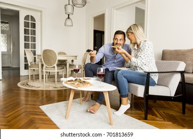 Young couple enjoying eating pizza and watching tv at home