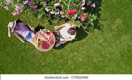 Jóvenes parejas disfrutando de comida y bebida en el hermoso jardín de rosas en una cita romántica, vista aérea desde arriba de hombres y mujeres comiendo y bebiendo juntos al aire libre en el parque