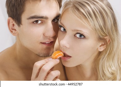 Young couple enjoying fruit breakfast in bed