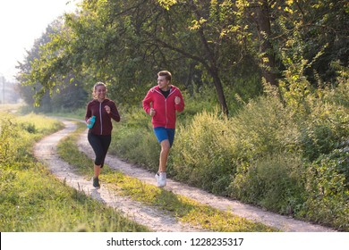 young couple enjoying in a healthy lifestyle while jogging along a country road, exercise and fitness concept