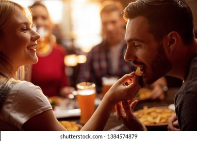 Young couple enjoying in lunch with their friends in a restaurant. Young man is being fed by his girlfriend with nacho chips.