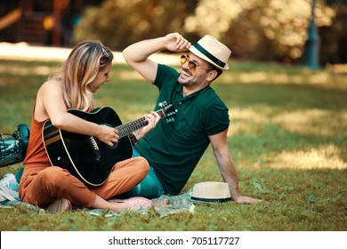 Young couple enjoying park and playing guitar.