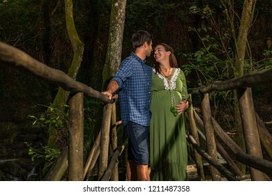 Young couple enjoying pregnancy on a natural idilyc scenery of a wooden bridge.