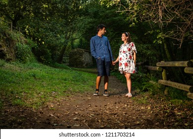 Young couple enjoying pregnancy walking on a natural idilyc scenery.