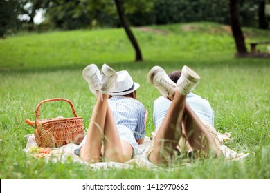 Young couple enjoying relaxing picnic time in a park. Lying on a picnic blanket with legs in the air, eating fruits. View from behind