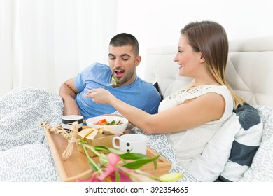 Young couple is enjoying romantic breakfast in bed. Young woman is feeding her boyfriend