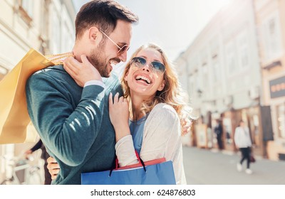 Young couple enjoying in shopping. Handsome young couple holding shopping bags on their shoulders while walking down the street after shopping. Consumerism, shopping, lifestyle, fashion